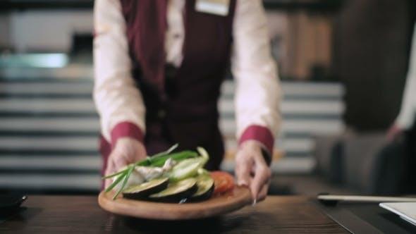 Waiter Delivers Vegetarian Dish For Grilling
