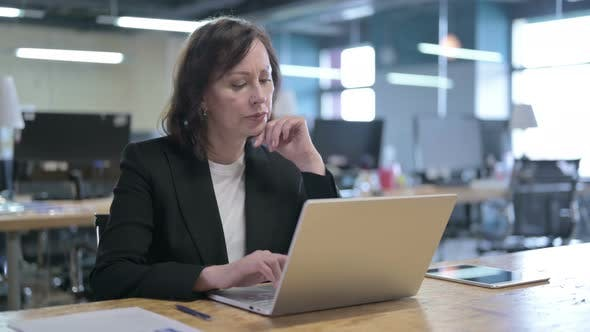 Thumbnail for Serious Middle Aged Businesswoman Thinking and Working on Laptop in Office