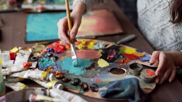 Cover Image for Paintbrush In Woman Hands Mixing Paints On Palette