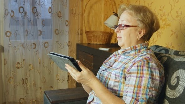 Thumbnail for Senior Woman Sitting In Sofa With Electronic Tablet
