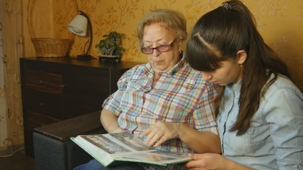 Thumbnail for Old And Young Woman Looking At Family Photo Album On Sofa At Home