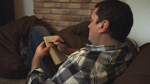 Der Mann schreibt To Do Liste im Notizbuch