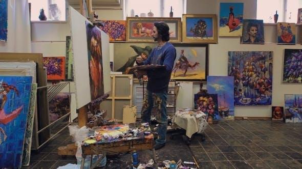 Thumbnail for Der Künstler malt mit Ölgemälde. Im Atelier, unter seinen eigenen Werken.