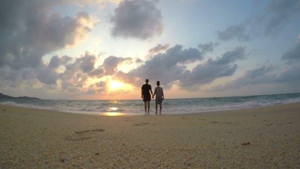 Thumbnail for UHD. Couple In Honeymoon On Beach At Sunrise By Sea