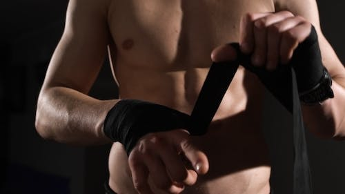 Mid Section Of a Shirtless Muscular Man Binds Bandage On His Hand