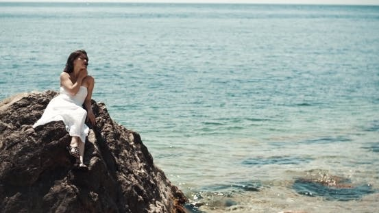 Thumbnail for Young Brunette Woman Siiting On The Rocks On Beach Near Waves