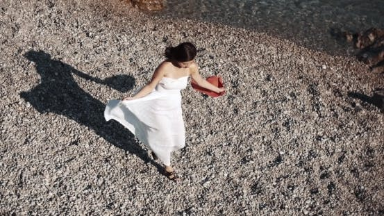 Thumbnail for Young Brunette Woman Walking On Pebbles Along The Sea