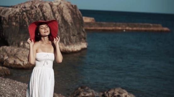 Thumbnail for Young Brunette Woman With Red Hat Walking Along The Sea