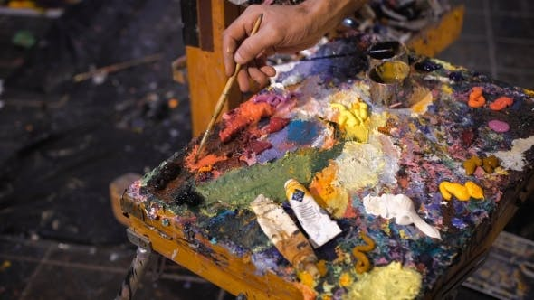 Thumbnail for Artist Mixes Oil Paints On Pallet With Various Colors