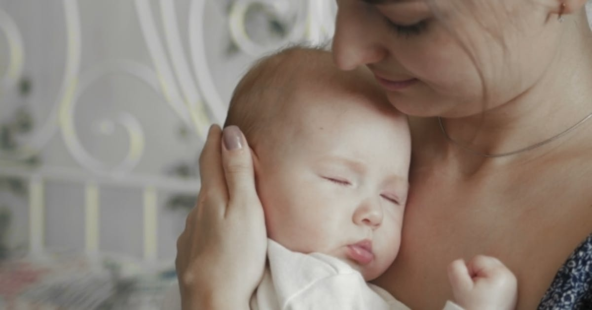 Young Mother Holding Her Newborn Sleeping Child
