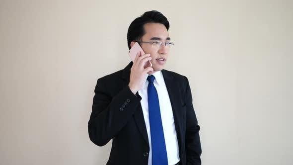 Asiatischer junger Geschäftsmann telefoniert.