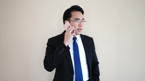 Asian young businessman talking at phone.
