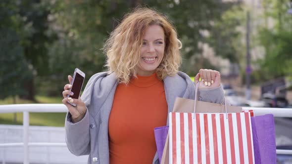 Thumbnail for Positive Young Red-haired Woman with Shopping Bags and Cellphone in Hands Jumping and Rising Hands
