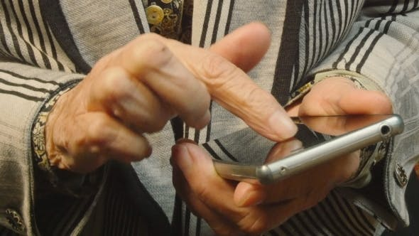 Cover Image for Hands Of The Old Woman And Smartphone.