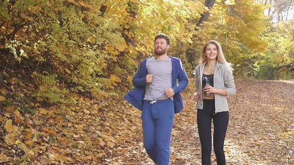 Man and Woman Doing Sports While Jogging in the Autumn Forest on a Sunny Day, Healthy Lifestyle