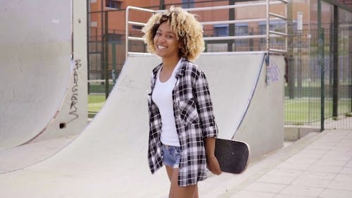 Charismatic Young Woman Holding a Skateboard
