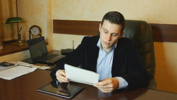 Thumbnail for Serious Young Businessman Looking Report In Office