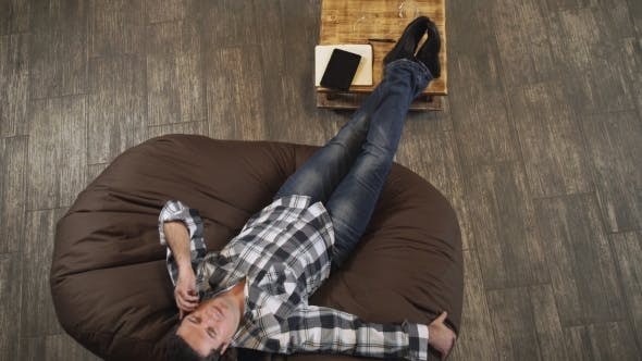 Cover Image for The Man Lies On a Sofa And Talking On The Phone.