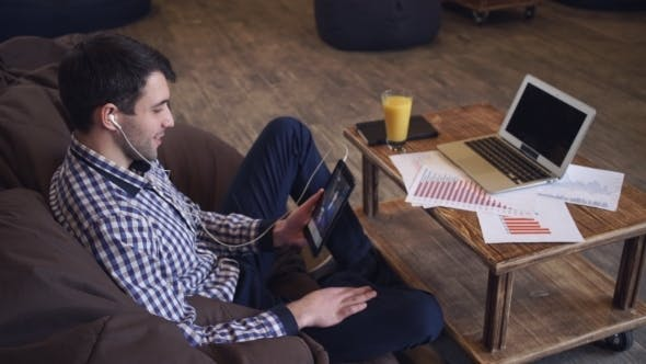 Thumbnail for Attractive Man Holding Tablet In Hand, Headphones Dressed, Online Conference
