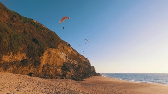 Thumbnail for Paragliders Fly Over The Ocean Beach