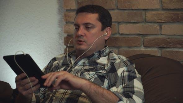 Thumbnail for Man In Earphone Talking Through Tablet.