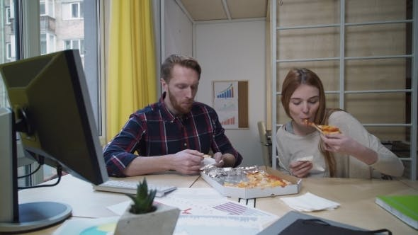 Workers Eat Pizza In The Office At The Workplace