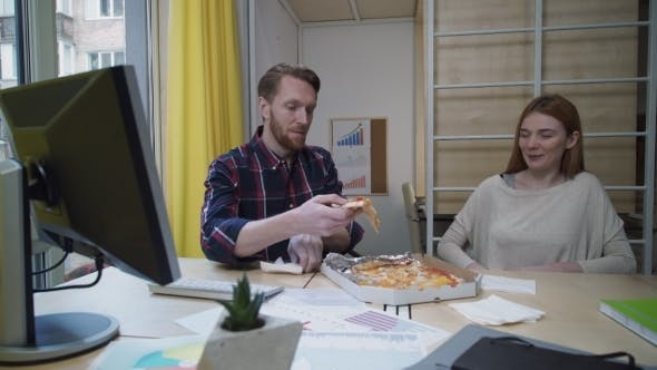 Cover Image for Man And Woman Eating Pizza At Workplace.