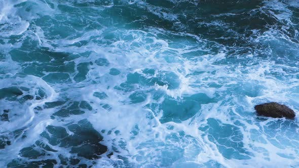 Dark Blue Sea Waves Crashing on the Rocks with White Foam in Slow Motion