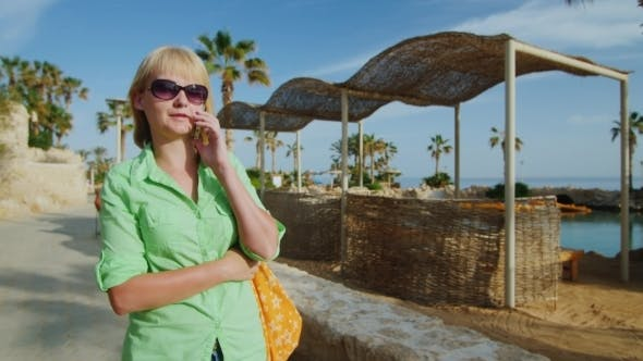 Thumbnail for Young Woman Walking On The Recreation Area, Talking On The Phone