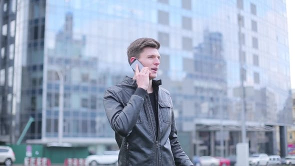 Cover Image for Brunette Guy Talking On a Mobile Phone On The Background Of The Business Center