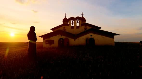Nun standing in front of Old Church and Sunset View