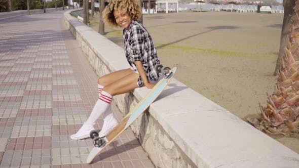 Thumbnail for Happy Trendy Young Woman With a Skateboard