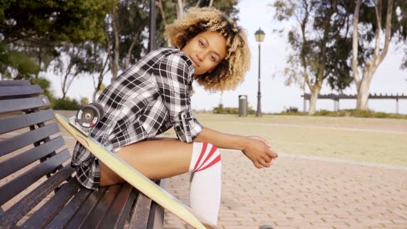 Young Woman With Skateboard On Bench