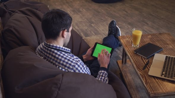 Thumbnail for A Man Sits On The Tablet, The Tablet On a Green Screen.