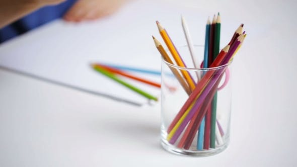Thumbnail for Colour Pencils In Glass And Girl Drawing On Paper