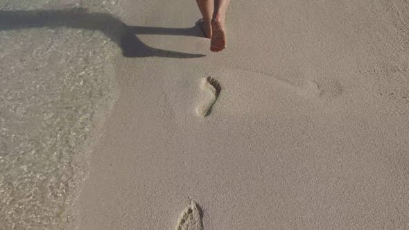 Thumbnail for Female Feet Walking On Sandy Beach With Footprints