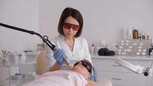 Cosmetician In Safety Glasses Using Laser For Facial Treatment