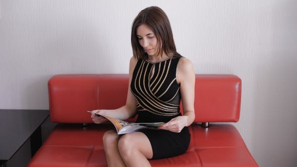 Thumbnail for Beautiful Young Brown Haired Girl Reading a Magazine