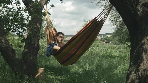 Man lying in hammock and blowing bubbles. Man blows bubbles while relaxing in hammock at garden