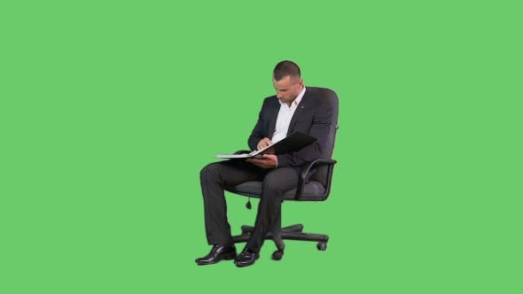 Thumbnail for A Man In An Armchair In a Jacket And a Green Background