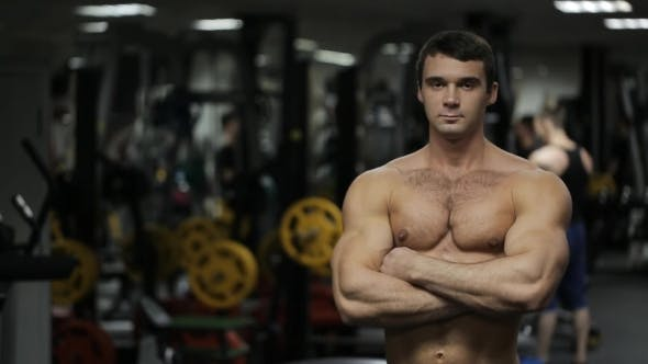 Thumbnail for The Man, Athlete, Personal Trainer With Steely Glance And Closed Posture Is Standing In The Gym