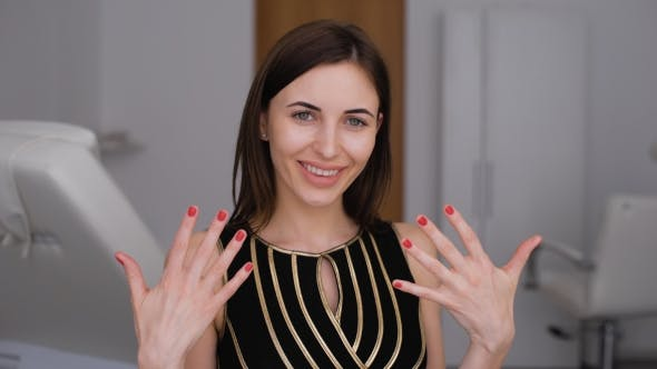 Thumbnail for Beauty Parlour. A Happy Girl Shows Off Her New Manicure. Red Nail