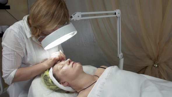 Thumbnail for Cosmetologist Look In Magnifier, Correct Eyebrow Of Adult Woman In Beauty Saloon