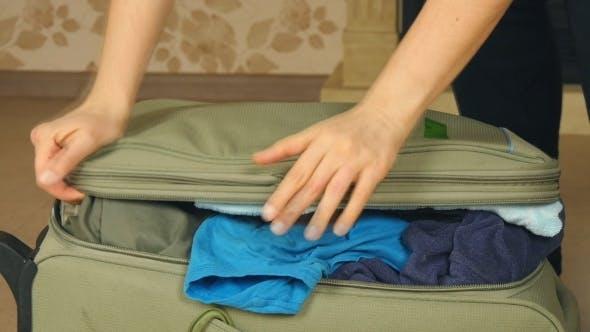 Jeune femme debout sur ses genoux sur valise surremplie, essayant de le fermer