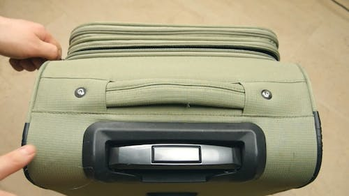 Detail Zip With Hand On a Suitcase