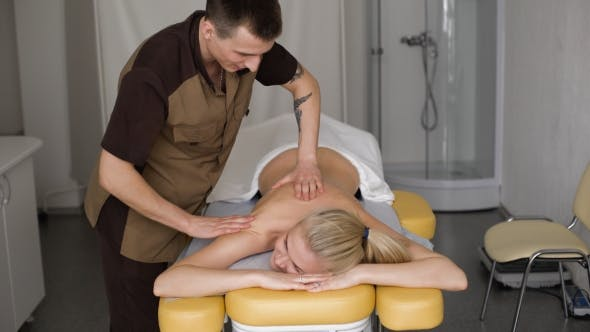 Thumbnail for Smiling Young Woman Getting Massage Treatment From Masseuse