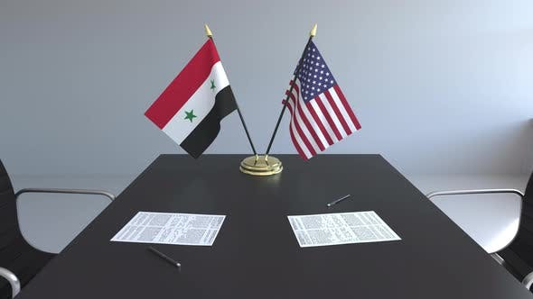 Flags of Syria and USA and Papers on the Table