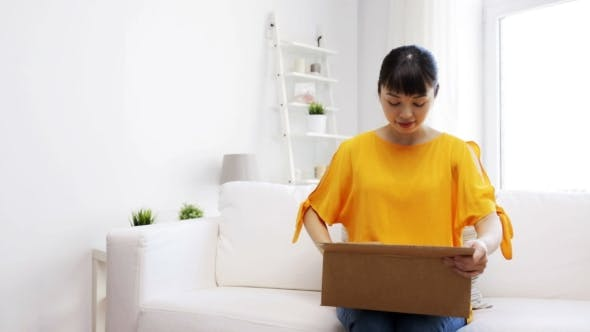 Thumbnail for Happy Asian Young Woman With Parcel Box At Home