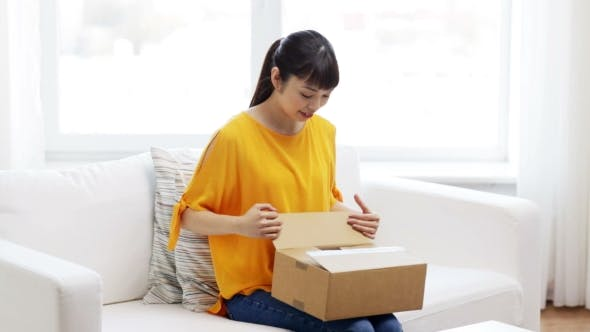 Cover Image for Happy Asian Young Woman With Parcel Box At Home