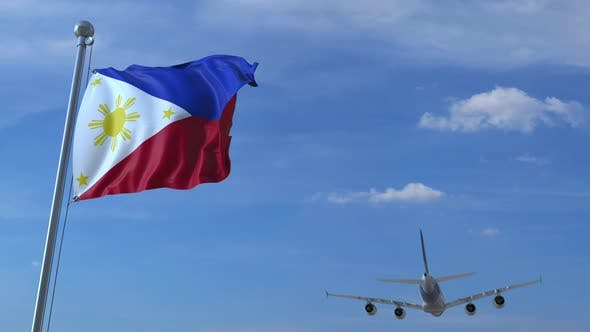 Commercial Airplane Landing Behind Waving Flag of the Philippines